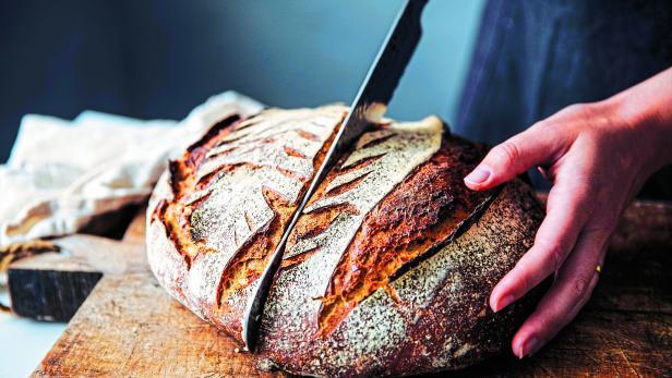 Woman cutting sourdough bread with knife on board